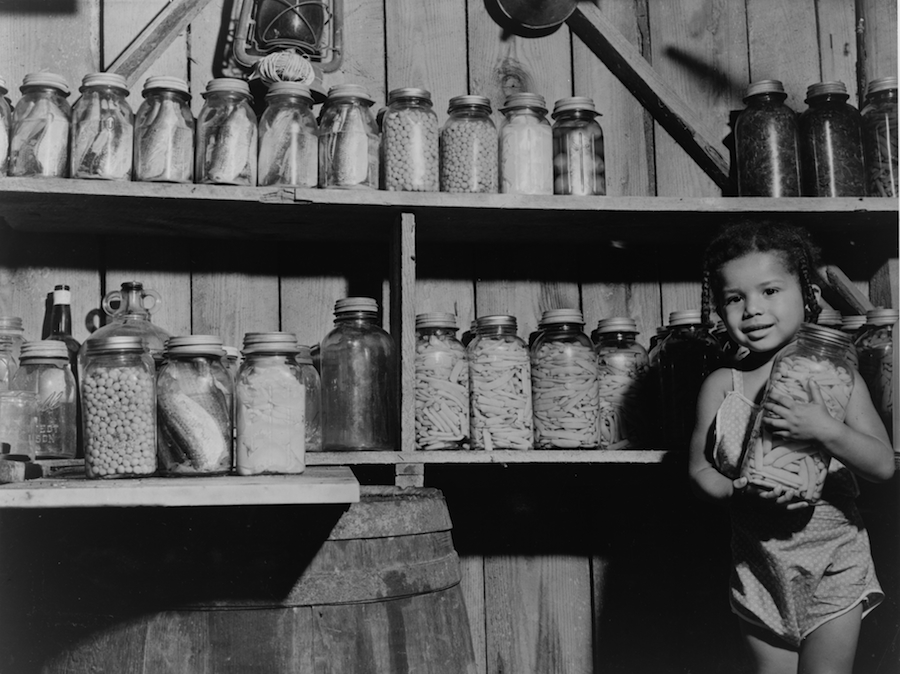 Dolores Harris, daughter of Farm Security Administration client George Harris, with canned food prepared by her mother, Dameron, Md., August 1940