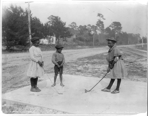 African American Girls And Boy Practicing Golf