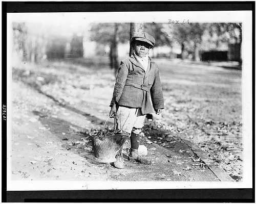 African American Boy Carrying Pale of Coal