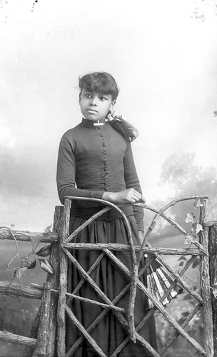 Girl holding a fan standing behind a gate